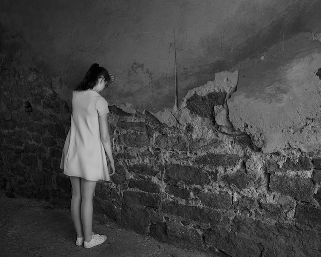 Samotna płacząca młoda dziewczyna stoi naprzeciwko starego ceglanego muru, widok z tyłu, czarno-biała, kopia przestrzeń