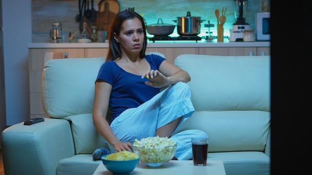 Samotna przestraszona kobieta w pokoju oglądając telewizję wieczorem i jedząca popcorn. zszokowana, skoncentrowana, zdumiona, sama nocą w domu, kobieta ze zdziwioną twarzą, patrząca na film trzymający w napięciu, siedząca na wygodnej kanapie