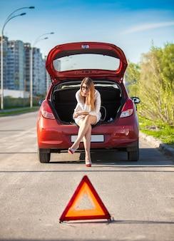Samotna przygnębiona kobieta siedzi na bagażniku zepsutego samochodu