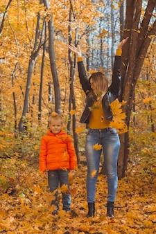 Samotna rodzina bawiąca się jesiennymi liśćmi w parku szczęśliwa mama i syn rzucają jesienne liście w górę