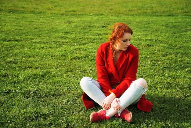 Samotna rudowłosa kobieta w czerwonym płaszczu i jasnych dżinsach siedzi na zielonej trawie w parku w ciągu dnia