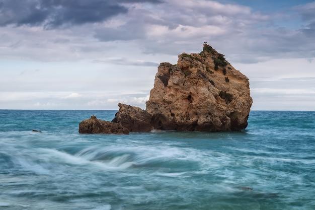 Samotna skała w morzu. ptaki odpoczywają na górze.