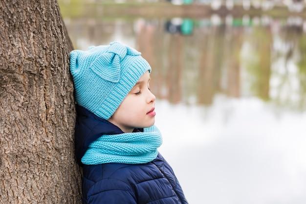 Samotna smutna dziewczyna stoi z zamkniętymi oczami przy drzewie nad brzegiem jeziora. zdrowie psychiczne. młodzieńcze lata