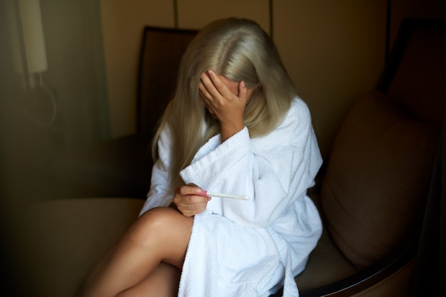 Samotna smutna kobieta narzeka na test ciążowy, siedząc na kanapie w salonie w domu