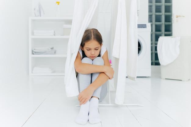 Samotna smutna mała dziewczynka siedzi na podłodze w pralni