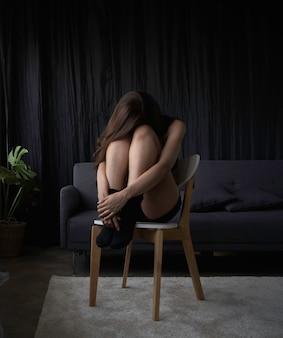 Samotność kobieta siedzi z kolanami ugiętymi na drewnianym krześle, zdenerwowana i stresująca