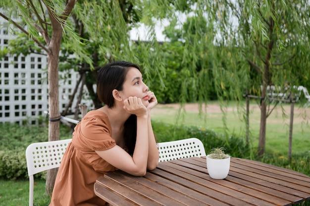Samotność młoda azjatycka kobieta siedzi i kładzie ręce na podbródku i patrzy na coś w ogrodzie