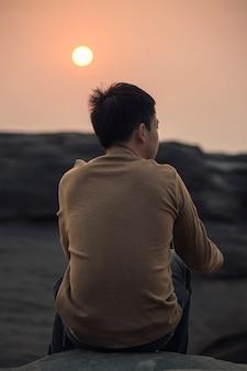Samotność młody azjata siedzi i patrząc na coś na skalnym klifie o zachodzie słońca