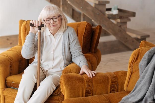 Samotność w domu. smutna, nastrojowa, zmartwiona kobieta siedząca w fotelu i zamykająca oczy, czując się samotna