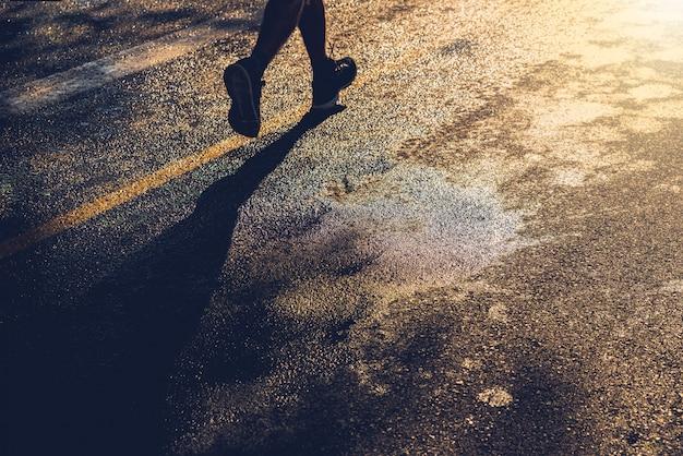 Samotny biegacz trenuje na mokrym asfalcie o zachodzie słońca