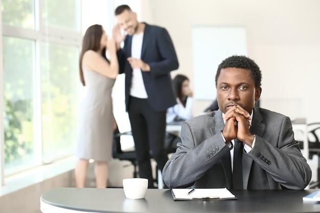 Samotny biznesmen afroamerykański w biurze. powstrzymaj rasizm