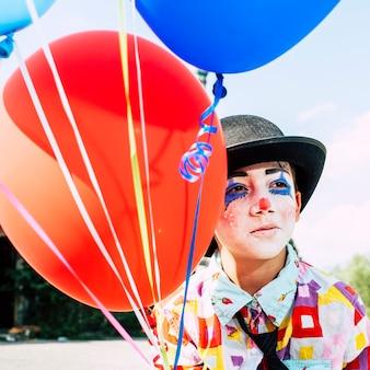 Samotny chłopiec w wieku 8/6 lat z makijażem klauna - smutny w kapeluszu i trzymający balony
