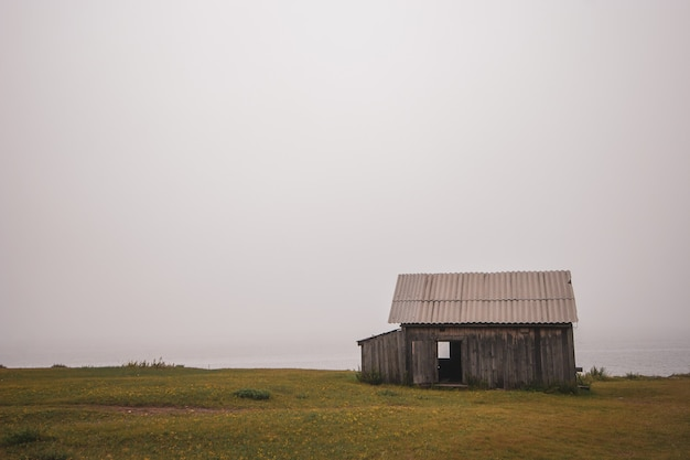 Samotny drewniany dom we mgle nad brzegiem jeziora bajkał