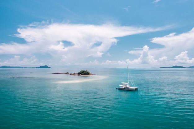 Samotny jacht dryfujący w lazurowym ciepłym oceanie, kierujący się na tajemniczą wyspę na środku oceanu. podróżujący. luksusowe wakacje. ciepły ocean. raj.