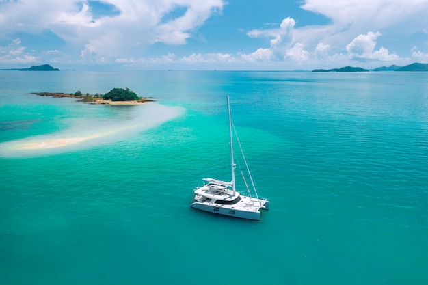 Samotny jacht żaglowy dryfujący w lazurowym ciepłym oceanie, kierujący się na tajemniczą zieloną wyspę na środku oceanu. podróżujący. luksusowe wakacje. ciepłe kraje. raj. turystyka.