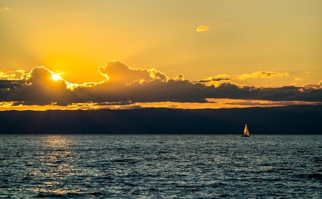 Samotny jacht żaglowy na jeziorze genewskim o zachodzie słońca w szwajcarii