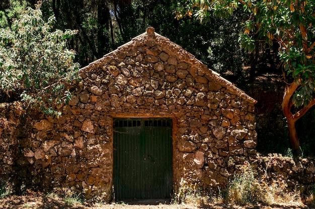 Samotny kamienny dom z drzewami