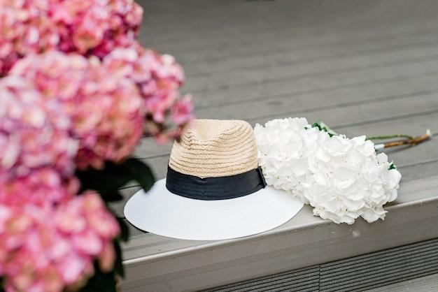 Samotny kapelusz i kwiaty biało-różowej hortensji. romantyczne tło wiosna i lato. miękka selektywna ostrość.