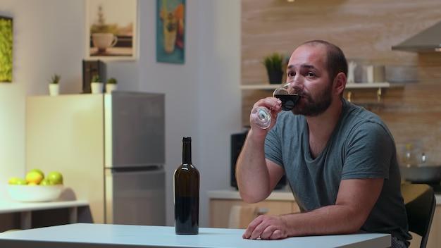 Samotny mąż pije kieliszek wina w domu. nieszczęśliwa osoba cierpiąca na migrenę, depresję, choroby i stany lękowe, wycieńczona z objawami zawrotów głowy, mająca problemy z alkoholizmem.