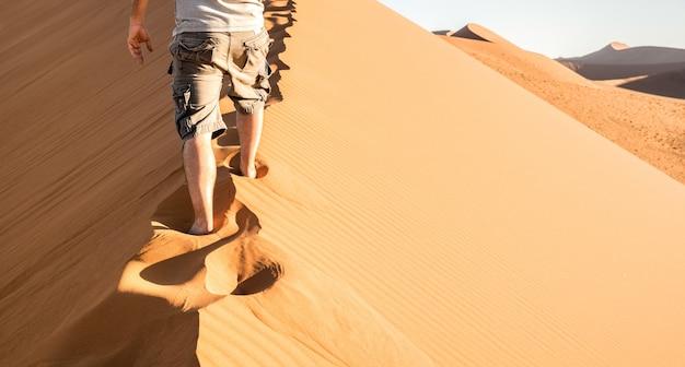 Samotny mężczyzna chodzenie na grzebieniu piasku na dune 45 na pustyni sossusvlei w namibii
