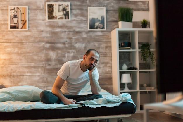 Samotny mężczyzna i znudzony oglądaniem telewizji w nocy w ciemnym pokoju.