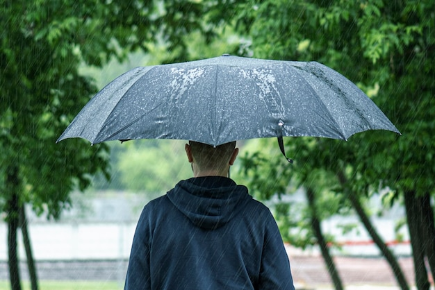 Samotny mężczyzna idący z czarnym parasolem podczas ulewnego letniego deszczu w padającym dniu w parku miejskim, obraz koncepcyjny pogody