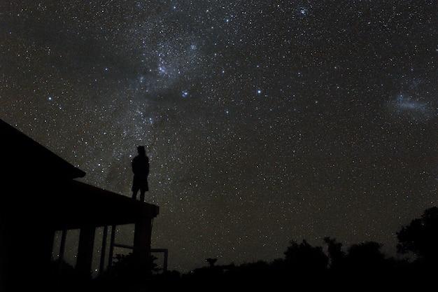 Samotny mężczyzna na dachu ogląda tajemniczą drogę i gwiazdy na nocnym niebie