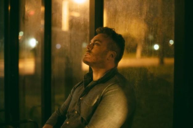 Samotny mężczyzna na dworcu autobusowym w mieście nocą