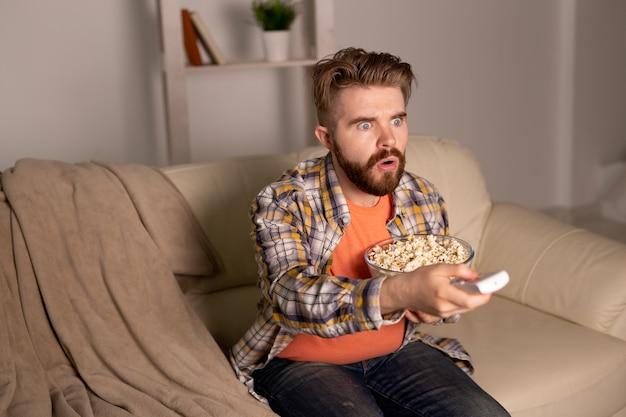 Samotny mężczyzna na kanapie przed telewizorem