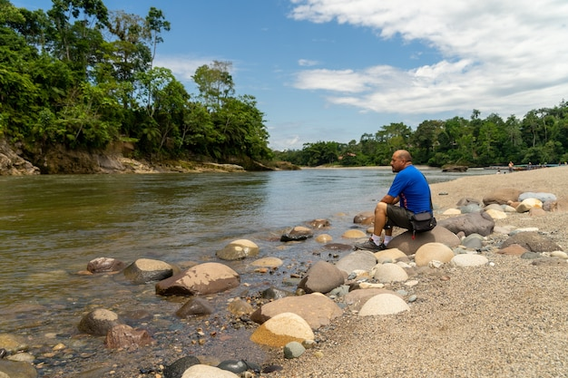 Samotny mężczyzna siedzący na brzegu rzeki w dżungli amazońskiej w ekwadorze