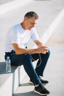 Samotny mężczyzna siedzący ze smartfonem w ręku