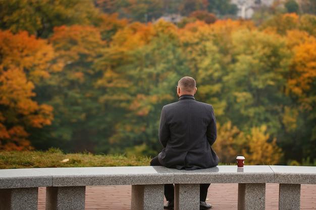 Samotny mężczyzna siedzi na kamiennej ławce i patrząc na naturę. widok z tyłu. jesienny motyw.