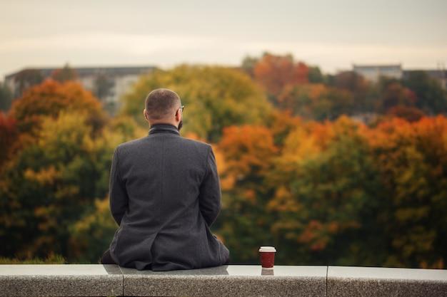 Samotny mężczyzna siedzi na kamiennej ławce i patrząc na naturę.