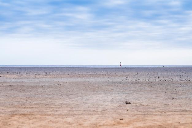 Samotny mężczyzna spacerujący samotnie po plaży na wybrzeżu pod błękitnym, ładnym niebem