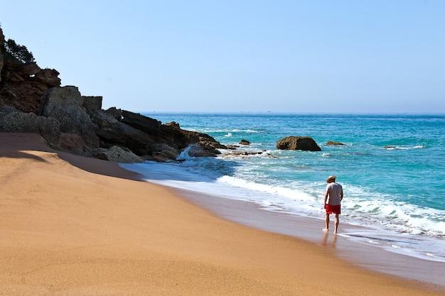 Samotny mężczyzna spaceruje po bezludnej plaży na wybrzeżu atlantyku w pobliżu kadyksu w hiszpanii.