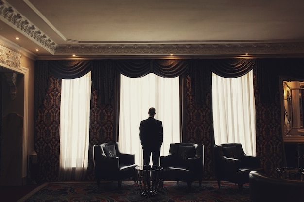 Samotny mężczyzna stoi przed oknem w pokoju