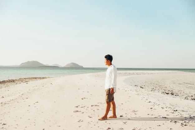 Samotny mężczyzna stojący na białej, piaszczystej plaży i patrzący na morze