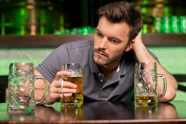 Samotny mężczyzna w barze. przygnębiony młody mężczyzna pijący piwo i trzymający rękę we włosach siedząc w barze