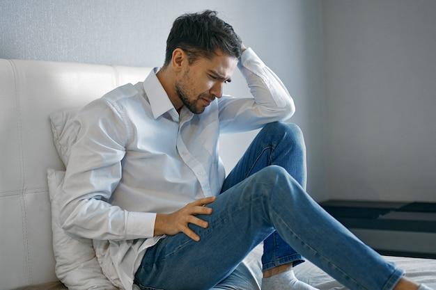 Samotny mężczyzna w koszuli i dżinsach siedzi na łóżku i trzyma dłonią głowę