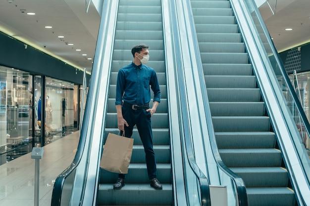 Samotny mężczyzna w masce ochronnej stojący na schodach schodów ruchomych. zdjęcie z miejscem na kopię
