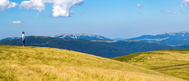 Samotny mężczyzna wycieczkowicz stojący na szerokim wzgórzu enjoing widok na góry