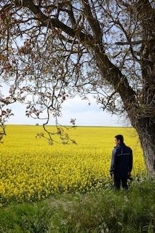 Samotny mężczyzna z aparatem stojący pod drzewem na polu z pięknymi żółtymi kwiatami
