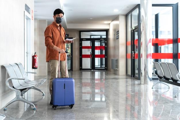 Samotny mężczyzna z walizką na stacji patrzący na telefon komórkowy