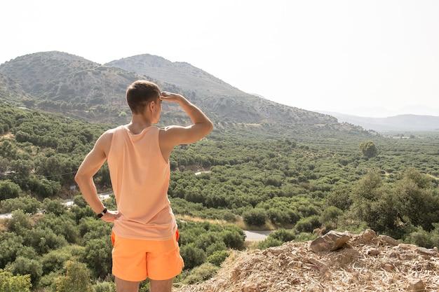 Samotny młody człowiek stoi na górze i patrzy w dal.