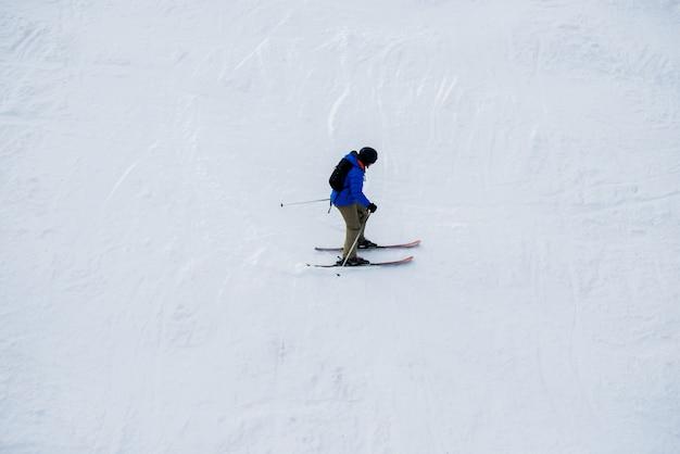 Samotny narciarz ze sprzętem na śniegu w ośrodku narciarskim.