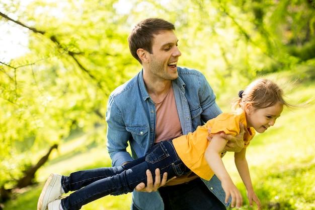 Samotny ojciec bawi się w parku ze swoją uroczą córeczką