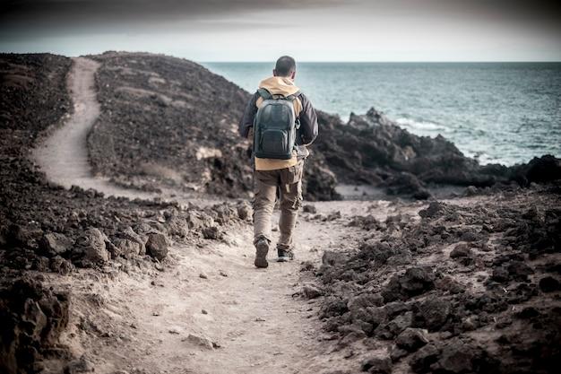 Samotny podróżnik, młody mężczyzna w średnim wieku, z ubraniami trekkingowymi i plecakiem, spaceruje po wybrzeżu oceanu na pustyni ze skałami
