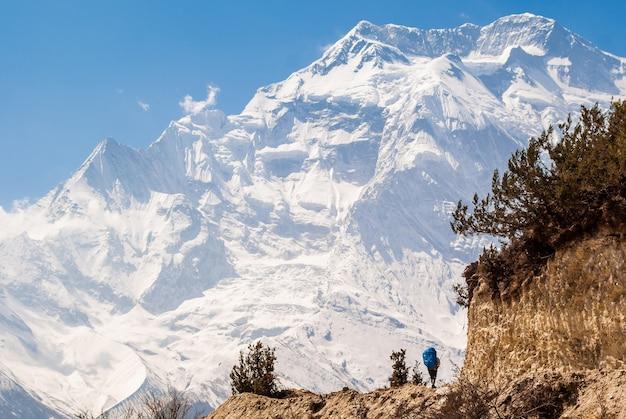 Samotny podróżnik z plecakiem spaceruje ścieżką w himalajach