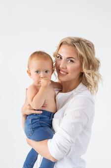 Samotny rodzic, macierzyństwo i koncepcja dziecka - wesoła matka zabawy z córeczką w studio, na białym tle.