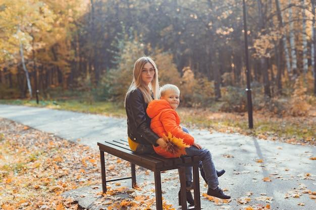 Samotny rodzic matka i dziecko chłopiec jesienią w parku siedzą na ławce w sezonie jesiennym i koncepcji rodziny